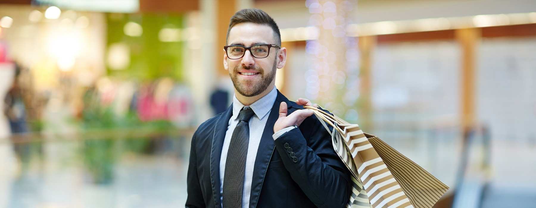 Man smiling holding a shopping bag